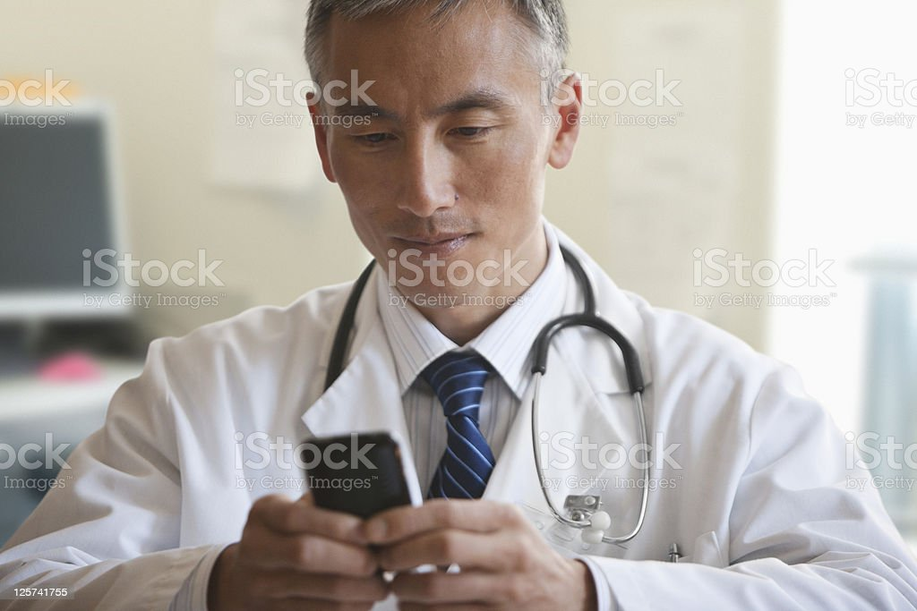 Mid-age doctor texting royalty-free stock photo