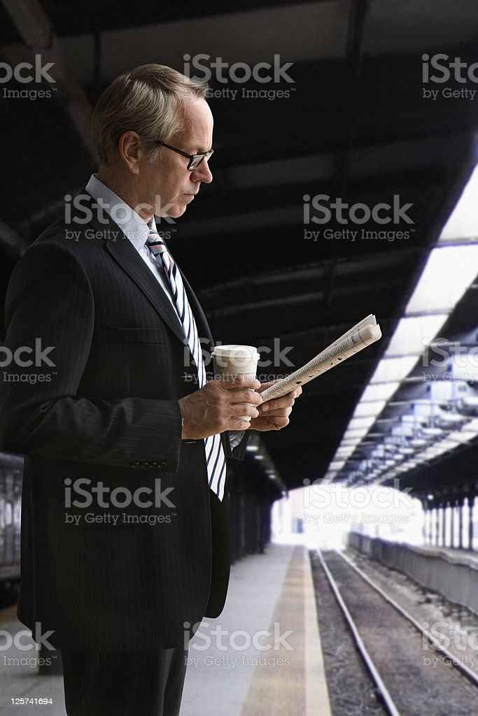 Mid-age man Reading news paper while waiting for the train royalty-free stock photo