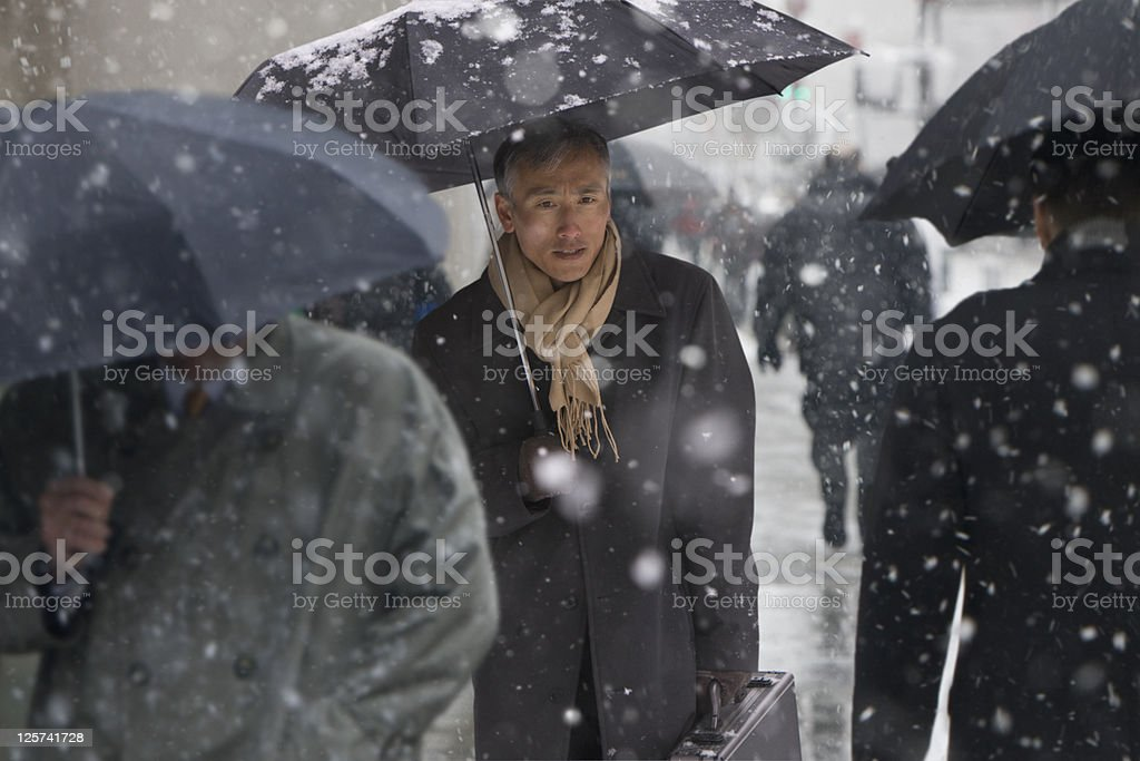 Mid-age man walking in the snow stock photo