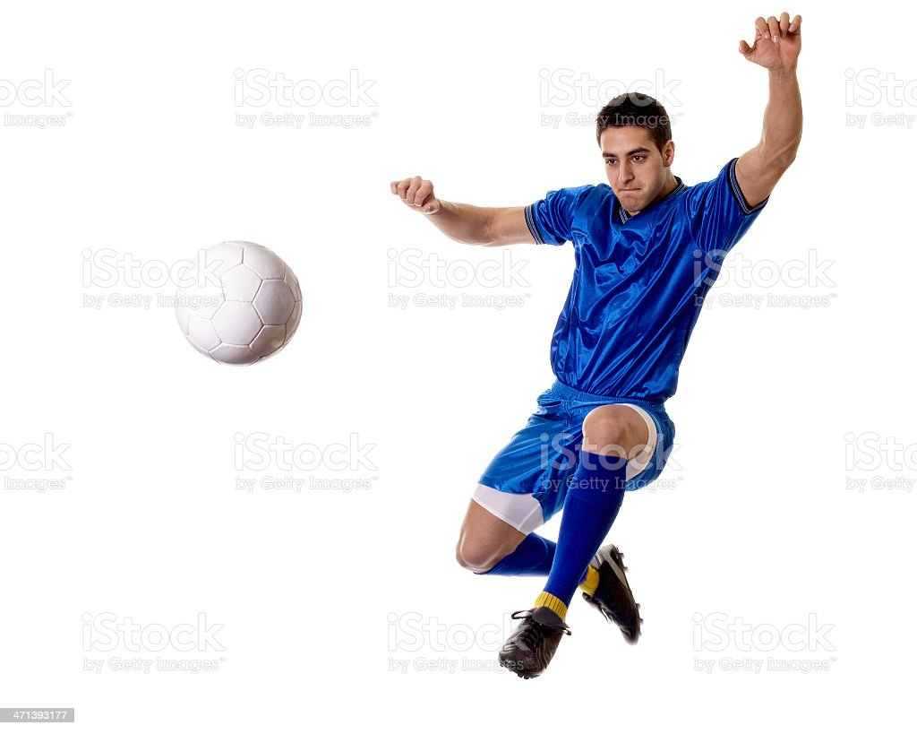 Mid-air candid shot of male soccer player kicking ball royalty-free stock photo