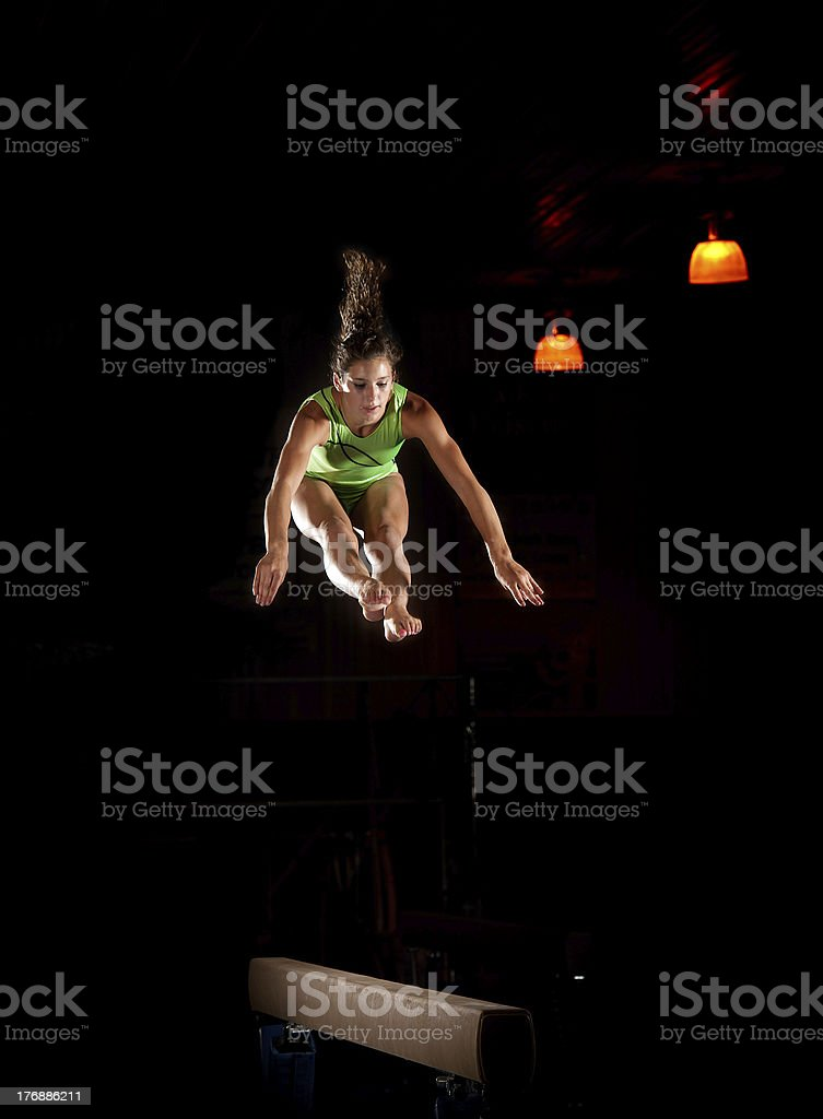 Mid-air leap from gymnast high above balance beam stock photo