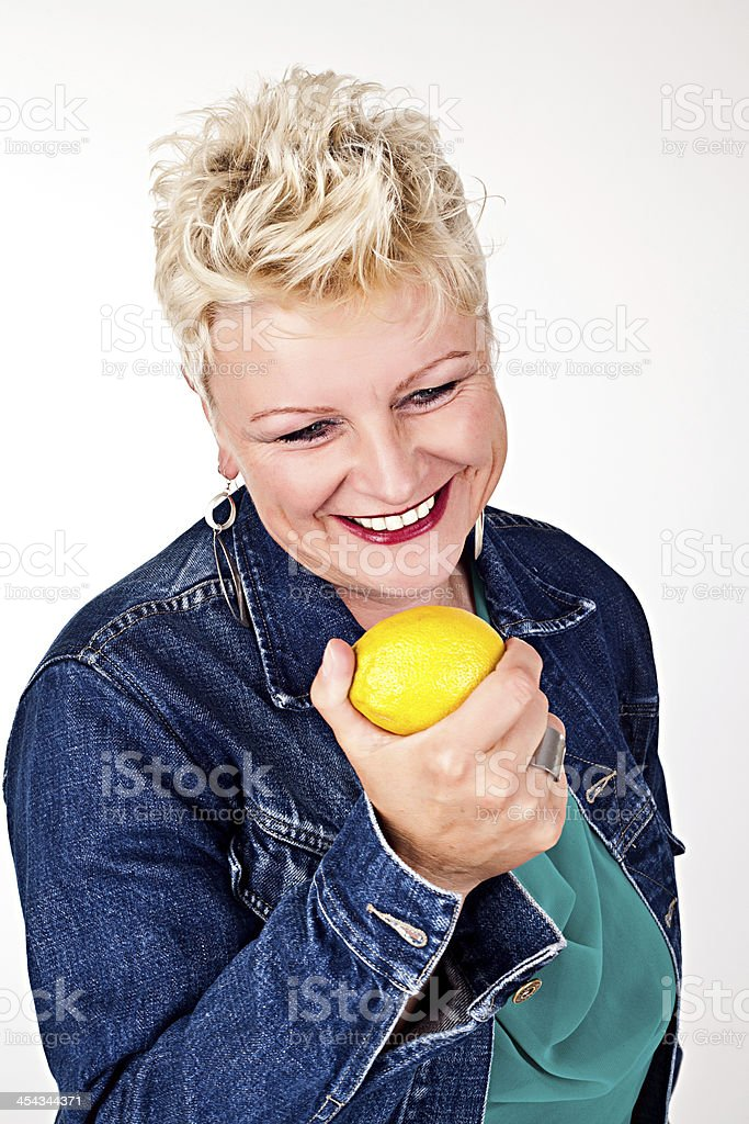 middelaged beautiful woman eating fresh lemon royalty-free stock photo