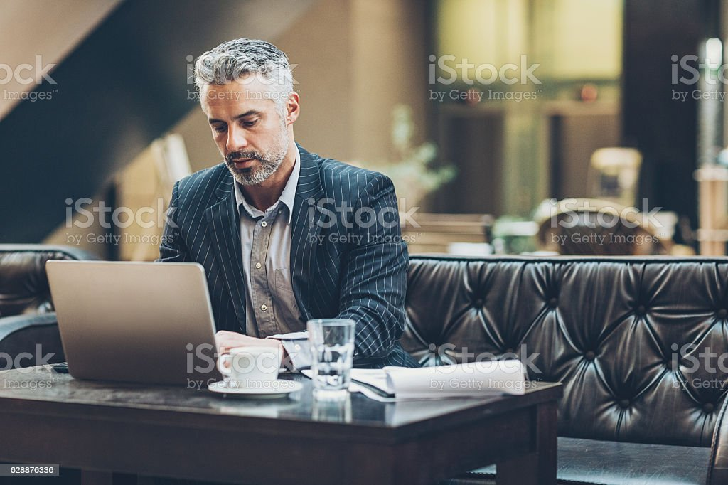 Middle age businessman working in comfortable environment stock photo