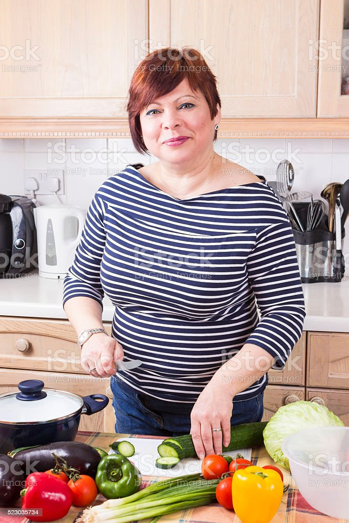 Middle age housewife cooking vegetables stock photo