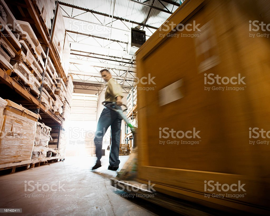 Middle Age Man in warehouse pulling shipping crate. royalty-free stock photo