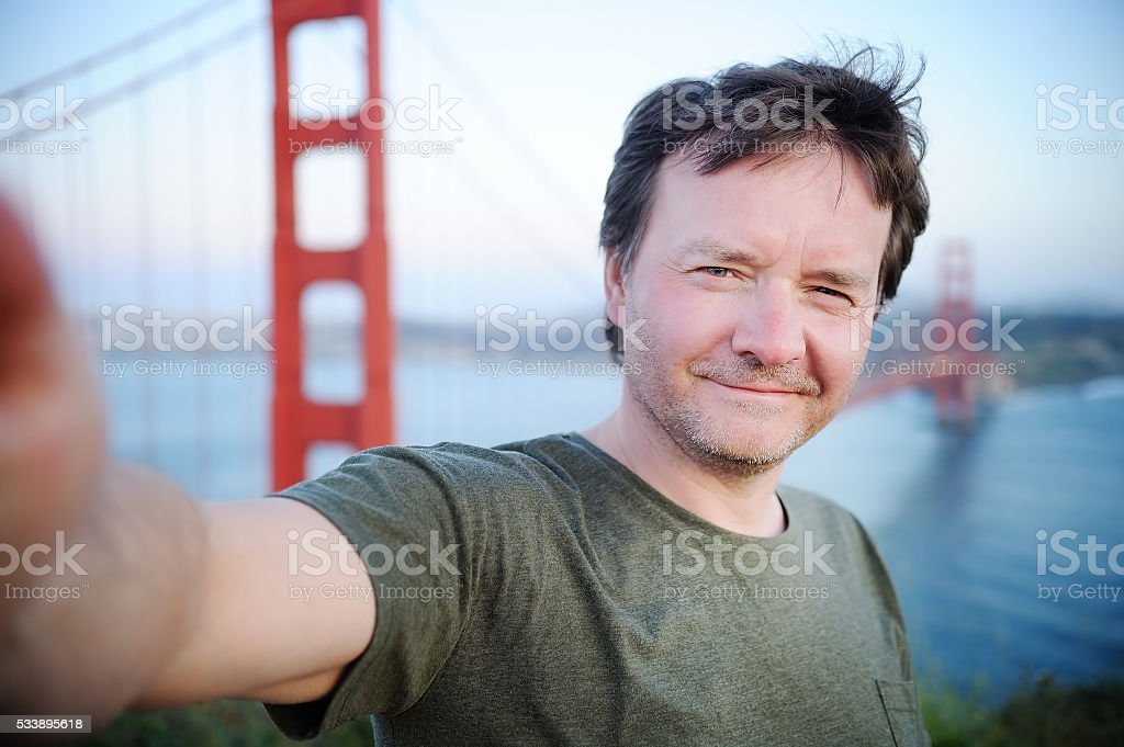 Middle age man making a self portrait with Golden Gate stock photo