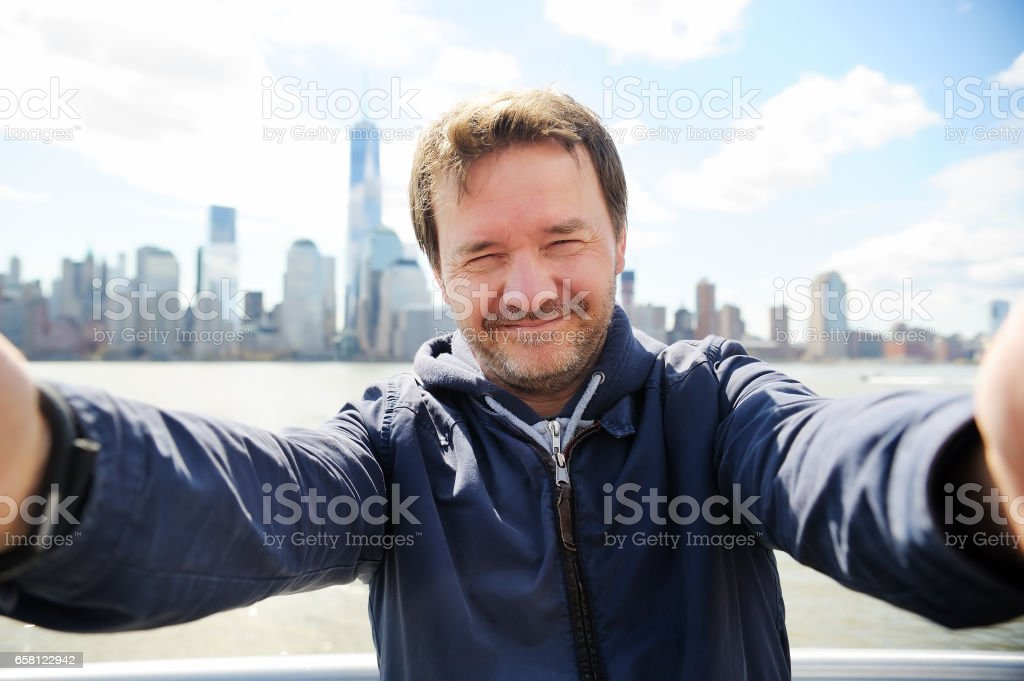 Middle age man making a self portrait (selfie) with Manhattan skyscrapers in New York City stock photo