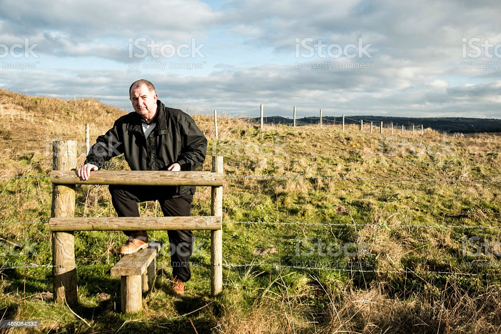 Middle age man using ladder stile across fence stock photo