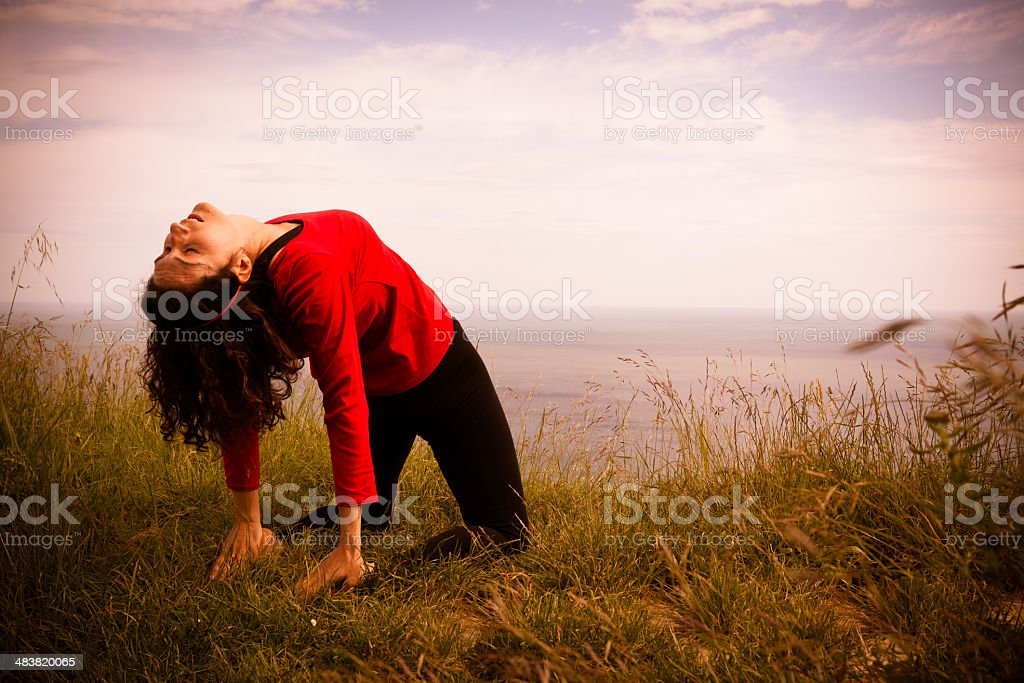 Middle age woman doing yoga exercise outdoors stock photo