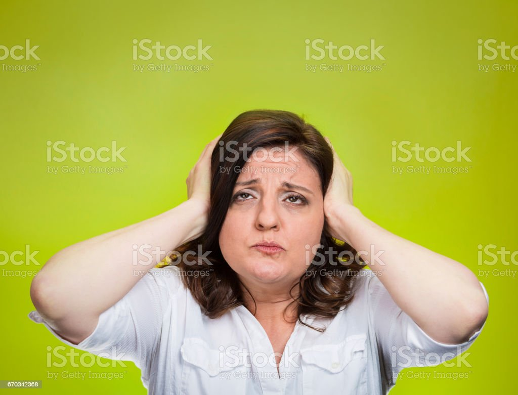 middle aged annoyed unhappy stressed woman covering ears looking up stock photo