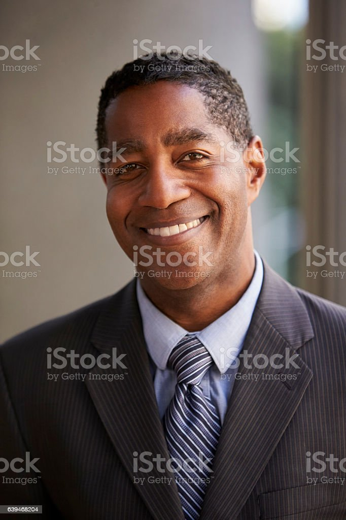 Middle aged black businessman smiling to camera, vertical stock photo