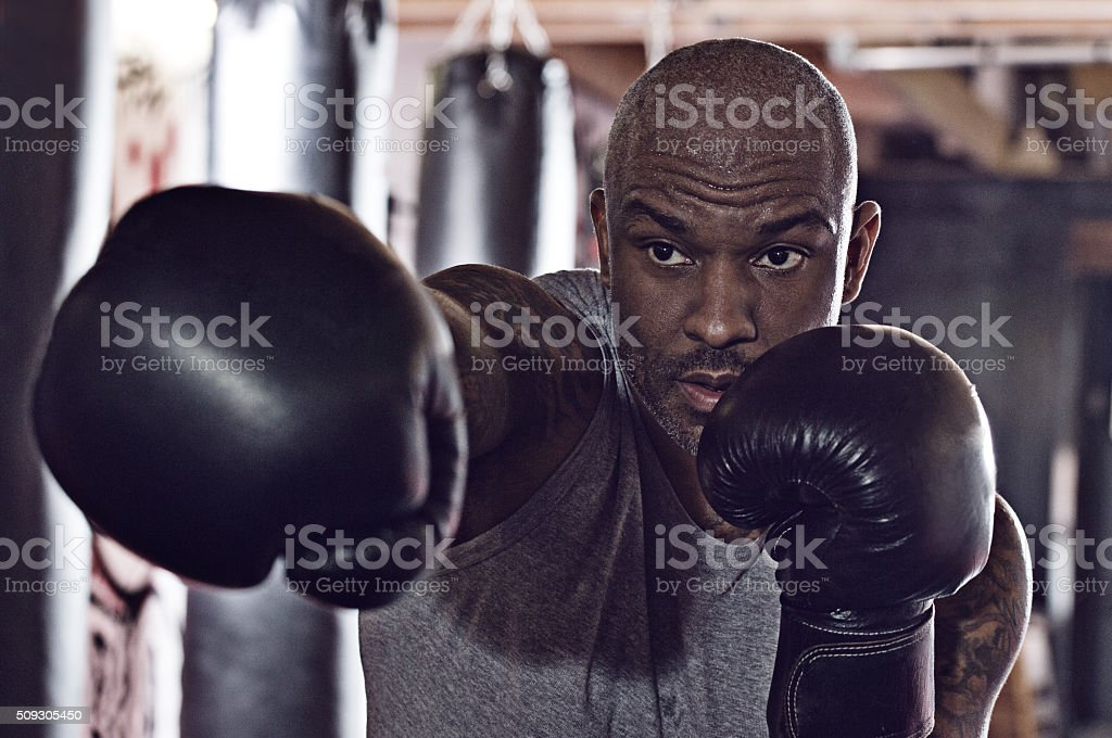 Middle aged black man at an urban styled boxing gym stock photo