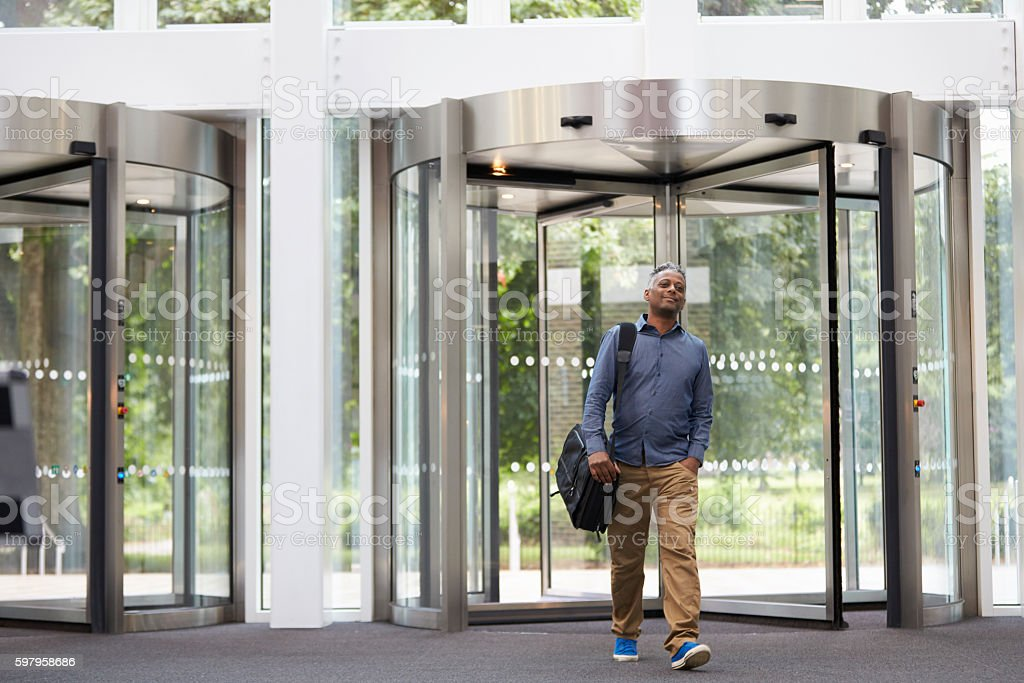 Middle aged black man entering the foyer of modern building stock photo