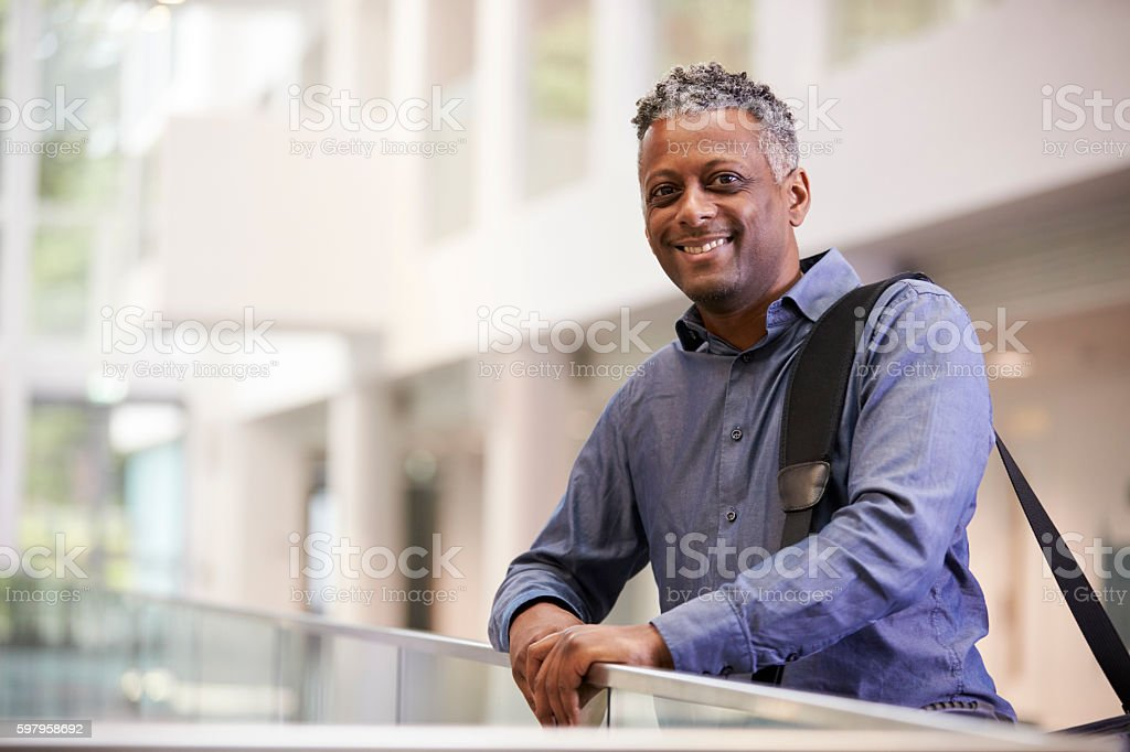 Middle aged black man  smiling in modern building lobby stock photo