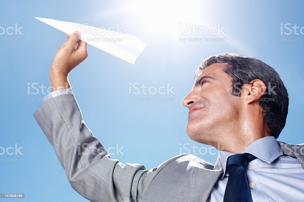 Middle aged business man launching paper aircraft royalty-free stock photo