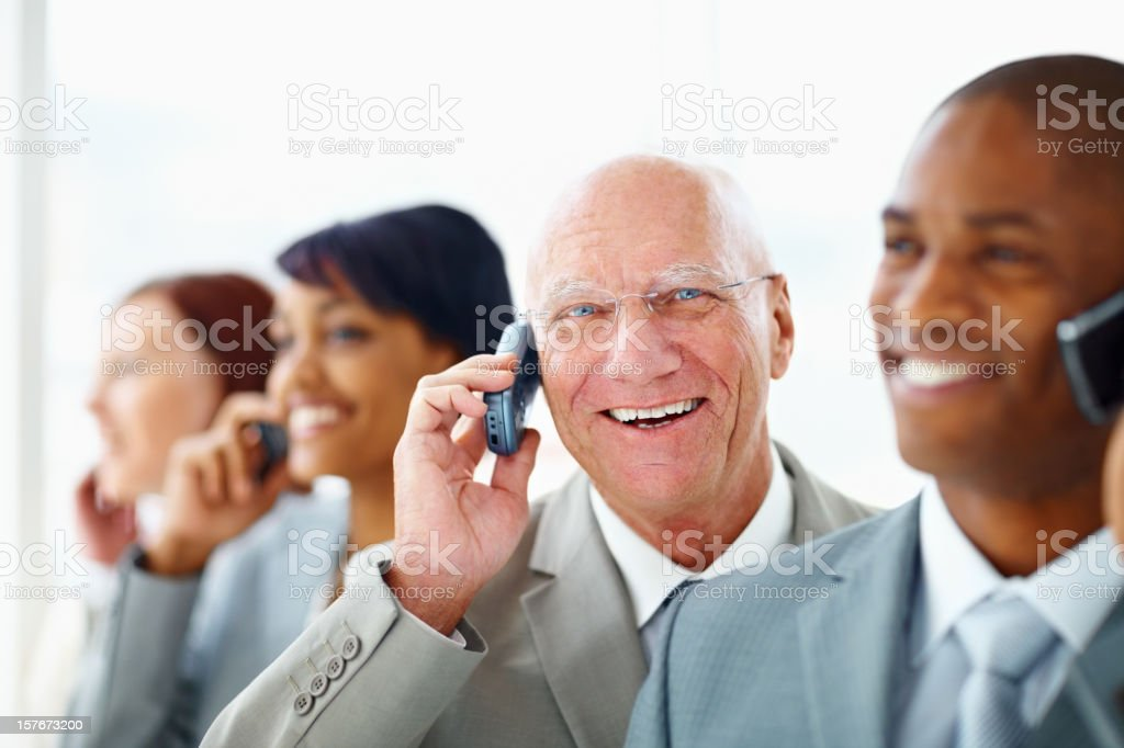 Middle aged business man with his team over the cellphones royalty-free stock photo