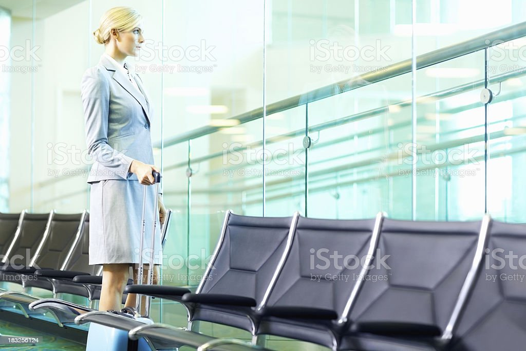 Middle aged business woman with luggage at airport looking away royalty-free stock photo