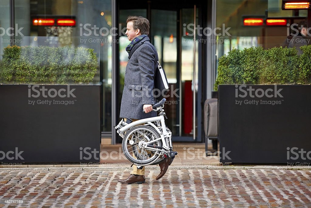 Middle aged businessman carrying his folding bicycle stock photo