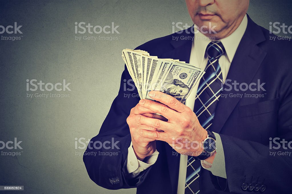 Middle aged businessman counting money stock photo