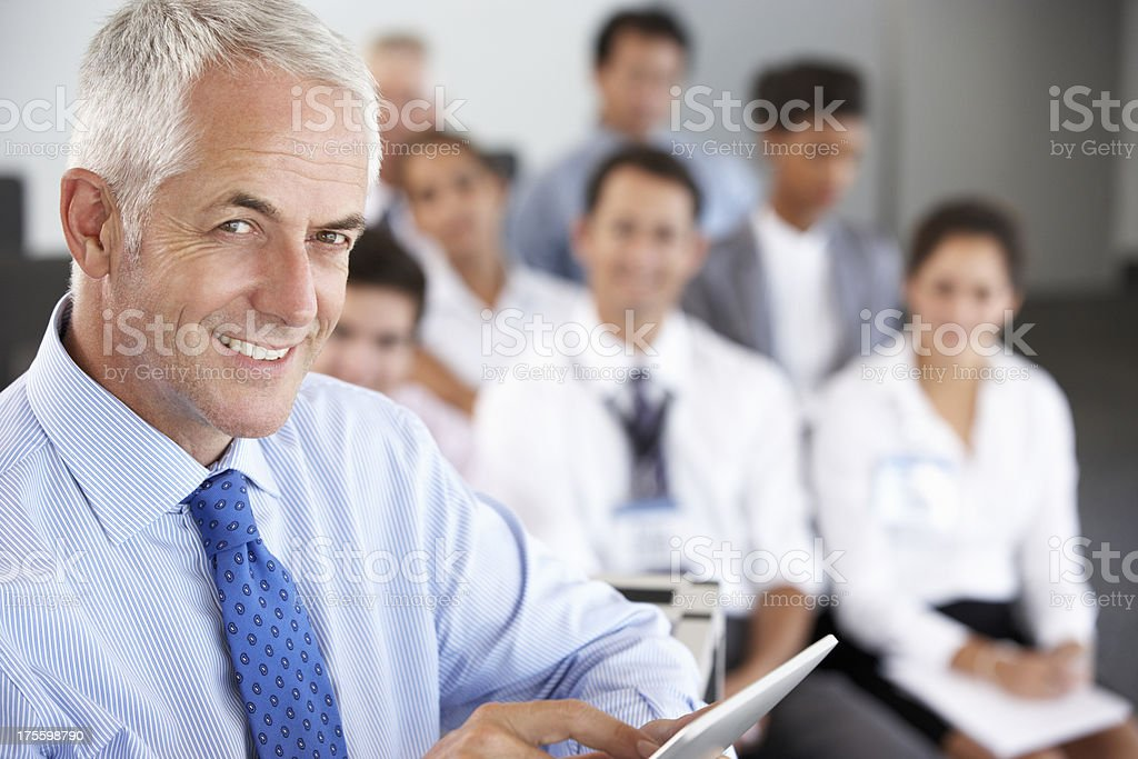 Middle Aged Businessman Delivering Presentation At Conference royalty-free stock photo