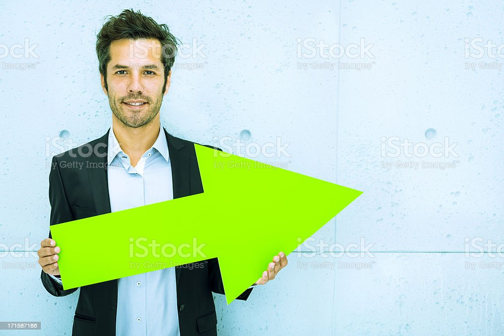 Middle aged businessman pointing right with green arrow stock photo