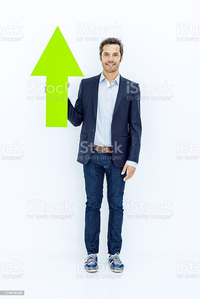 Middle aged businessman pointing up with green arrow stock photo