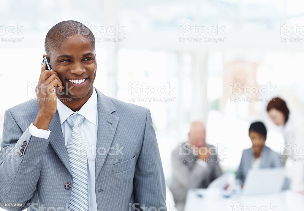 Middle aged businessman talking over cellphone and team in blur royalty-free stock photo