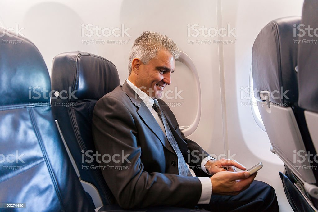middle aged businessman using cell phone on airplane stock photo