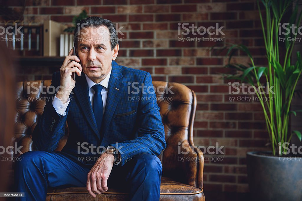 Middle aged businessman using mobile stock photo