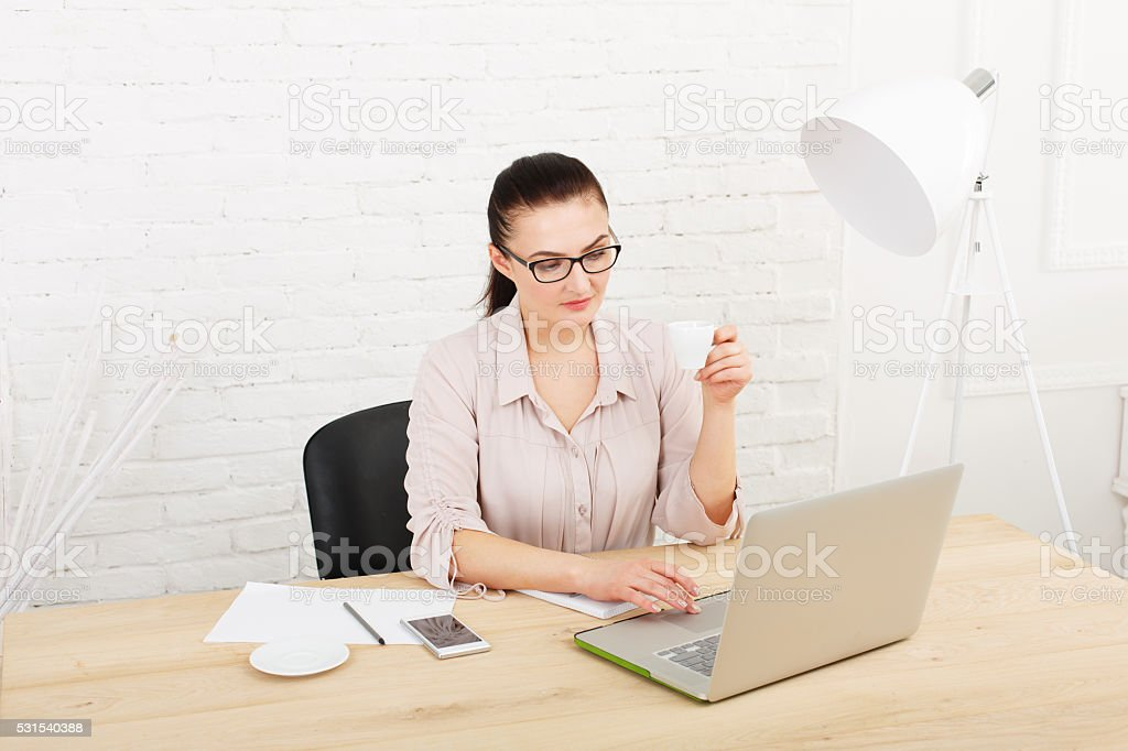 Middle aged businesswoman in office with laptop stock photo