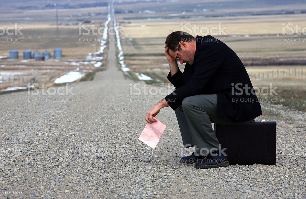 Middle Aged Caucasian Man Holding Pink Slip Beside Road royalty-free stock photo