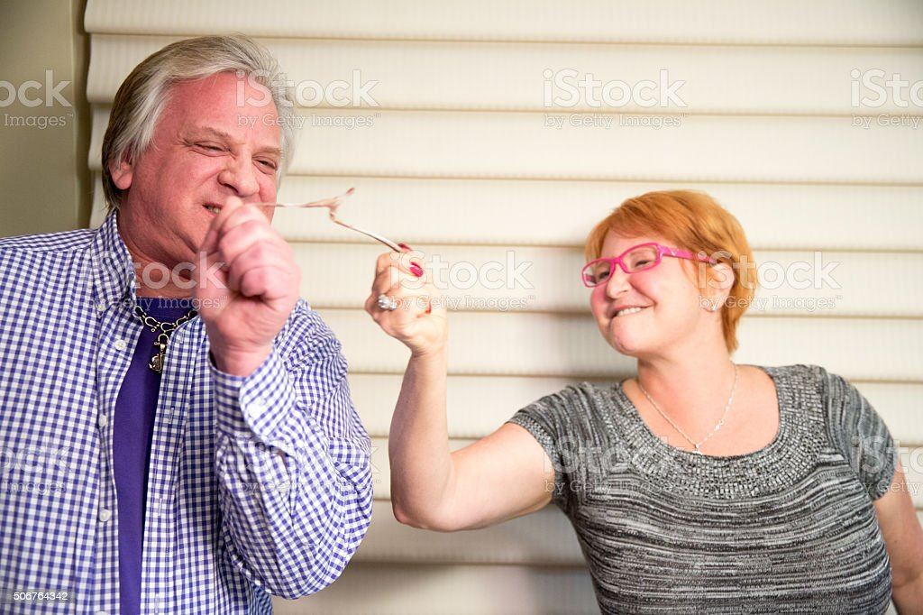 Middle aged caucasian siblings share the wishbone at Thanksgiving stock photo