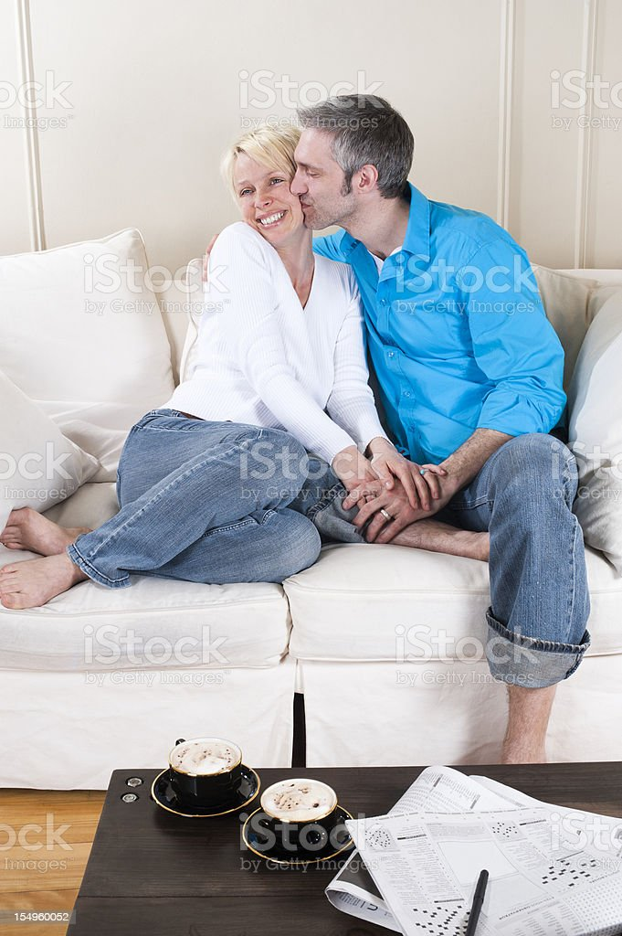 Middle aged coupe cuddling on a couch. royalty-free stock photo