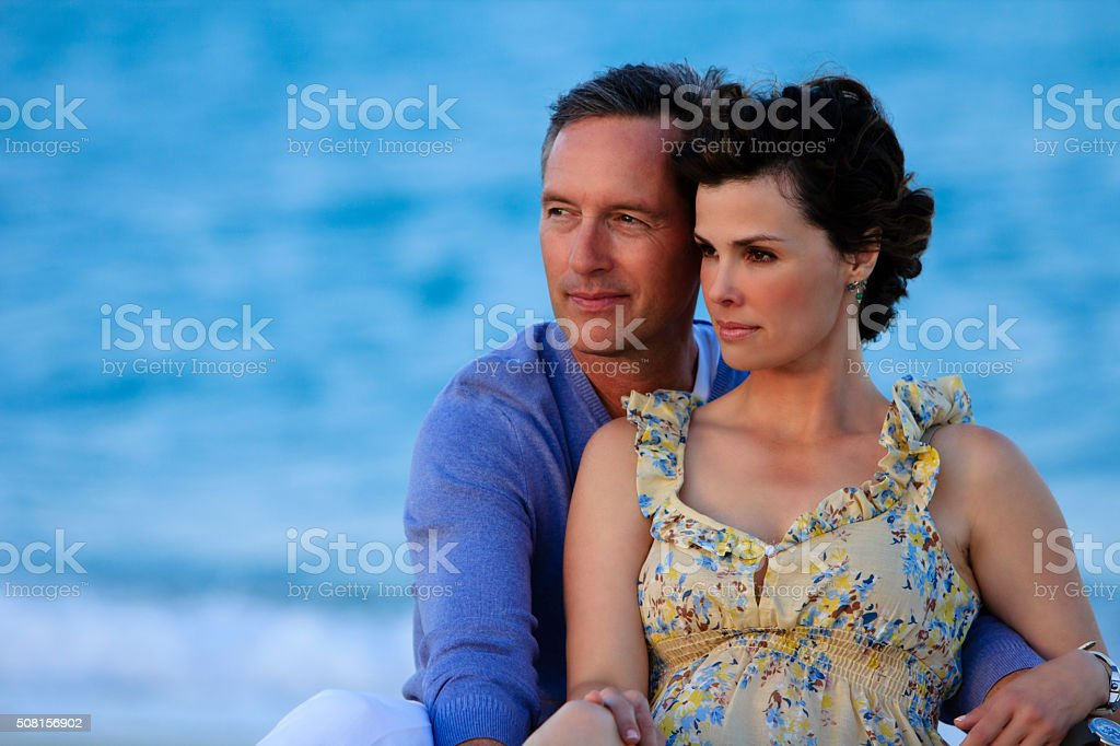 Middle aged couple gazing at the beach embracing stock photo