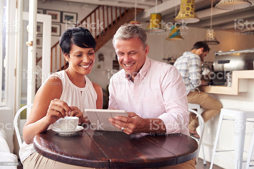 Middle aged couple in a cafe usuing a digital tablet stock photo