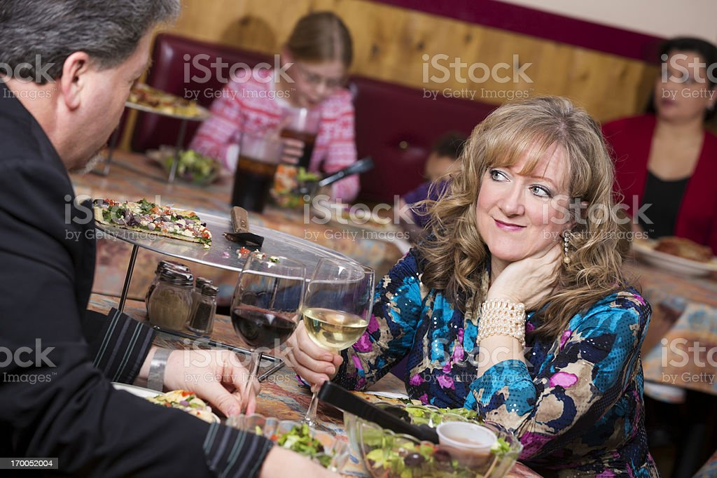Middle aged couple on a date at the busy restaurant royalty-free stock photo