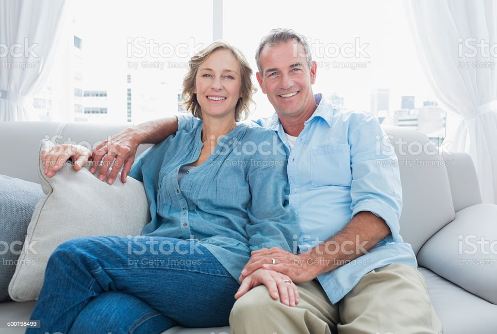Middle aged couple relaxing on the couch smiling at camera at home in...