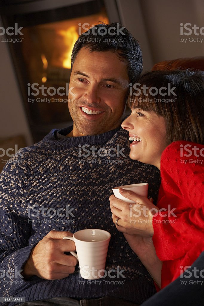 Middle Aged Couple Sitting On Sofa By Cosy Log Fire stock photo