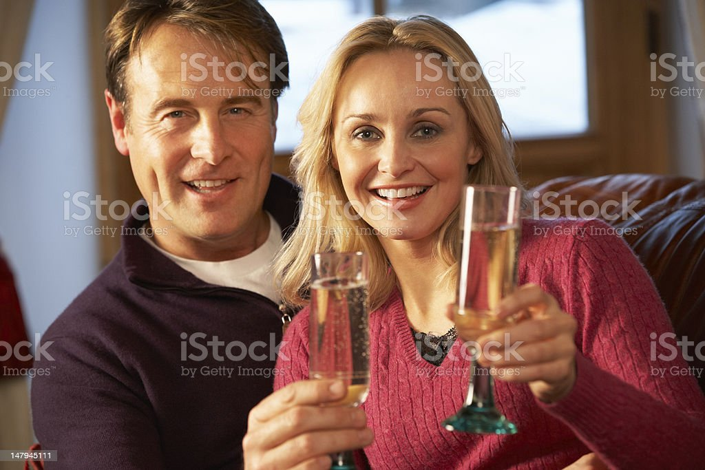 Middle Aged Couple Sitting On Sofa With Glasses Of Champagne royalty-free stock photo