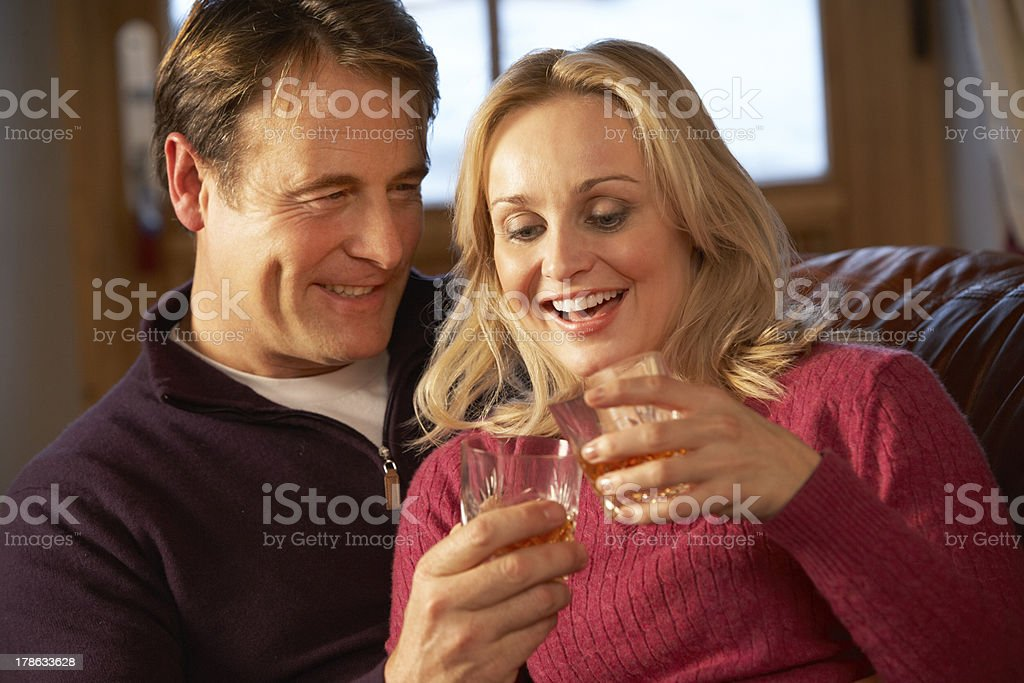 Middle Aged Couple Sitting On Sofa With Glasses Of Whisky royalty-free stock photo