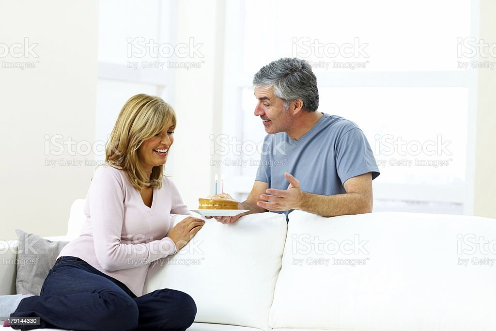Middle aged couple smiling holding a birthday cake royalty-free stock photo