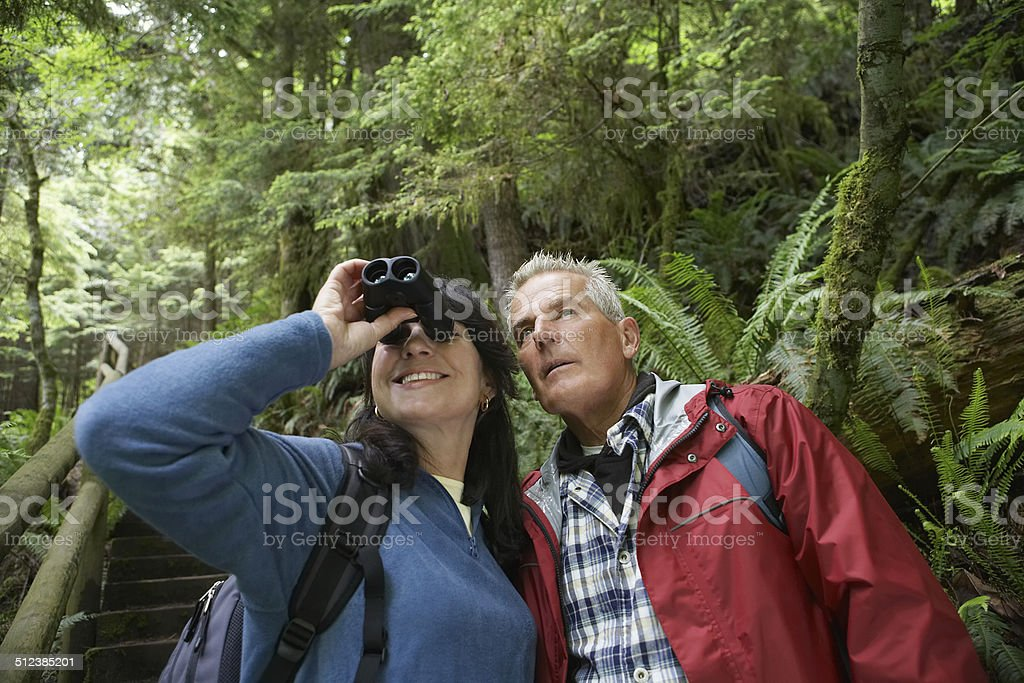 Middle Aged Couple With Binoculars In Forest stock photo