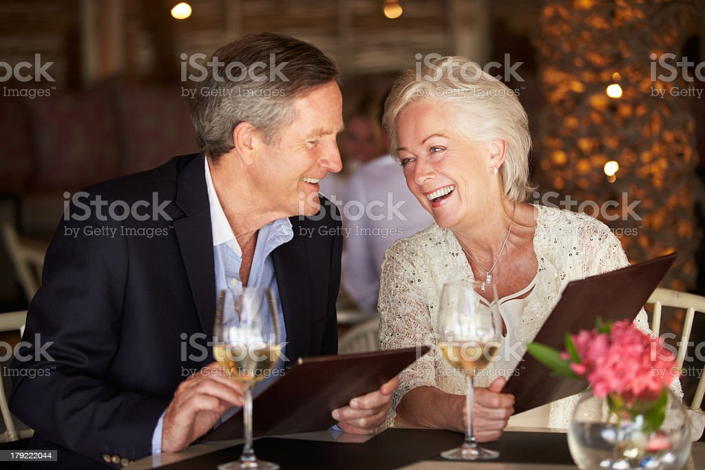 Middle aged couple with menus at fancy restaurant stock photo