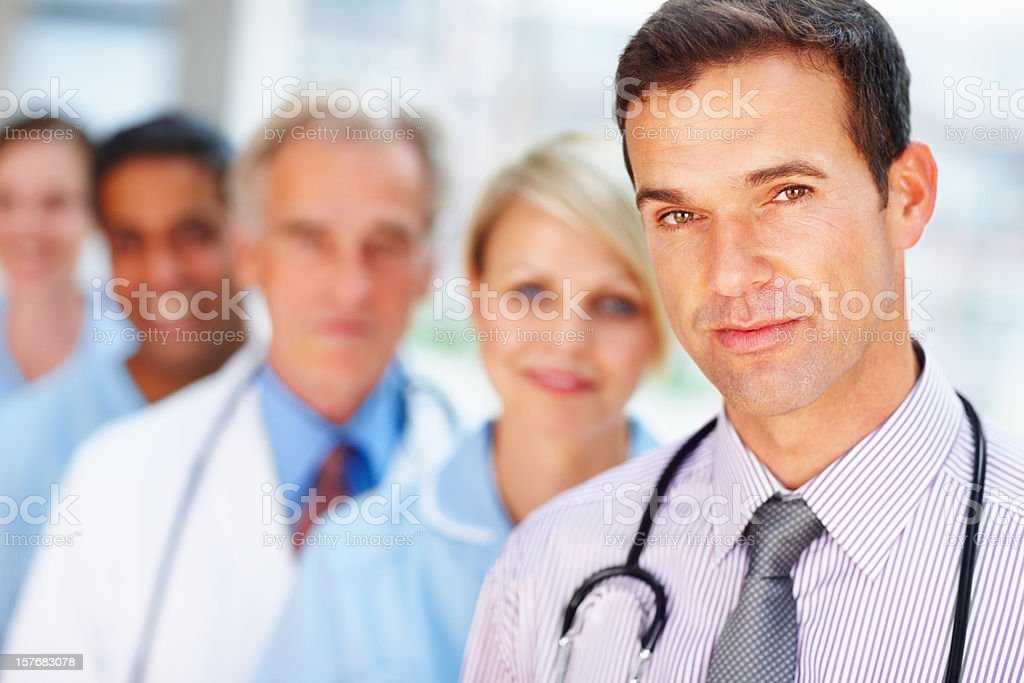 Middle aged doctor standing in front of his team royalty-free stock photo