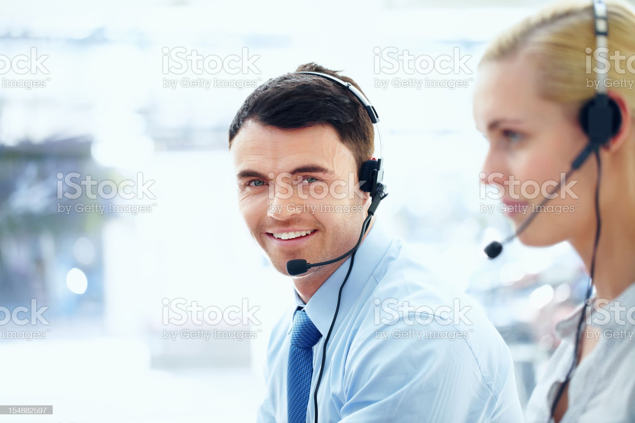 Middle aged executive wearing headset with his colleague royalty-free stock photo