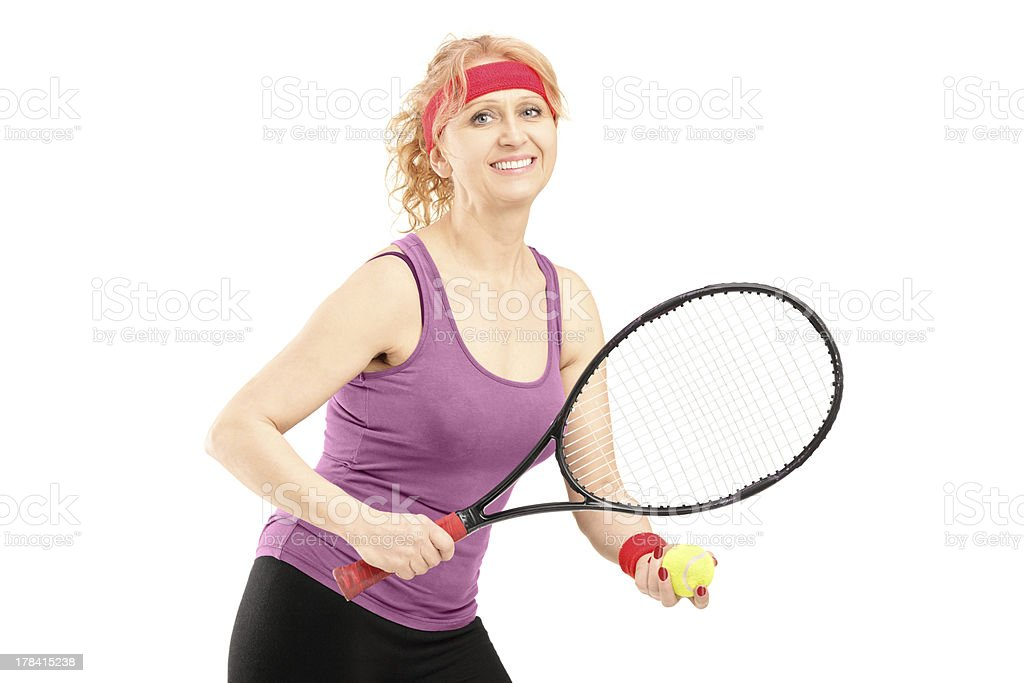 Middle aged female holding tennis racket and ball stock photo