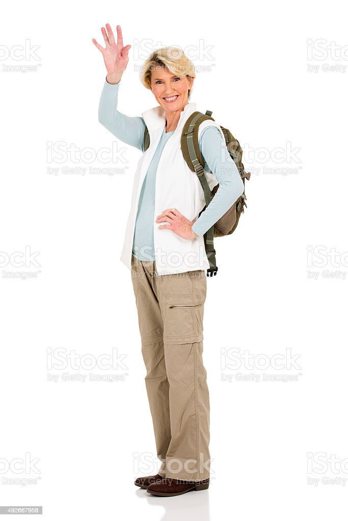 middle aged female tourist waving goodbye stock photo
