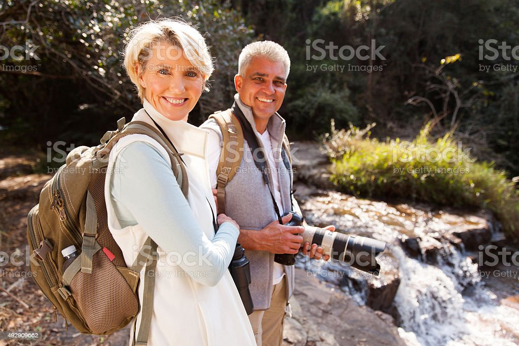 middle aged hikers relaxing by river stock photo