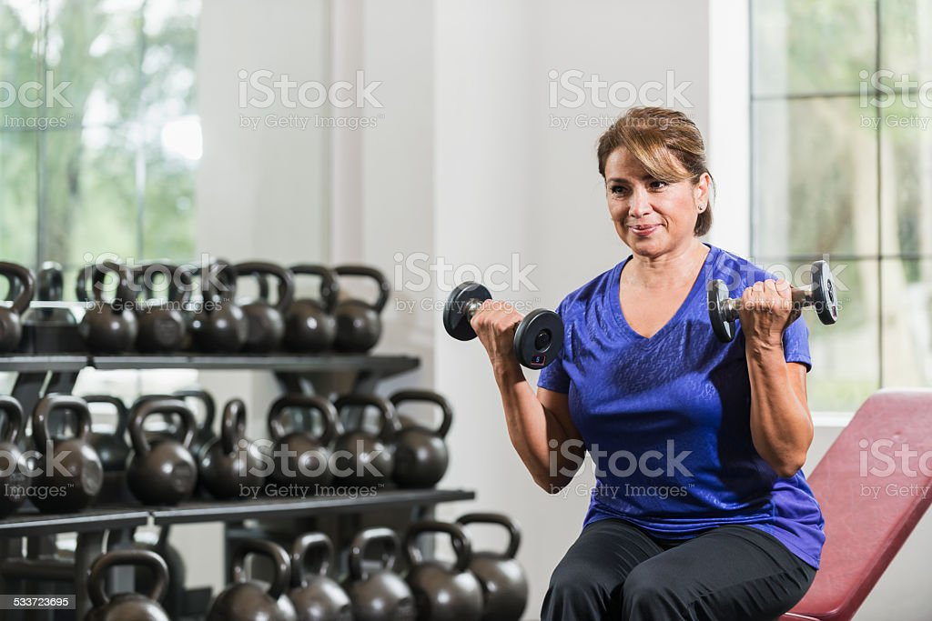 Middle aged Hispanic woman at gym lifting dumbbells stock photo