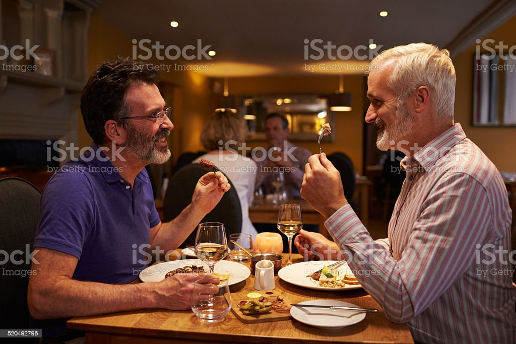 Middle aged male couple eating evening meal in a restaurant stock photo